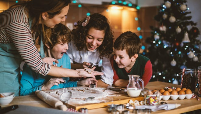 Mother and childrens making Gingerbread cookies for Christmas.
