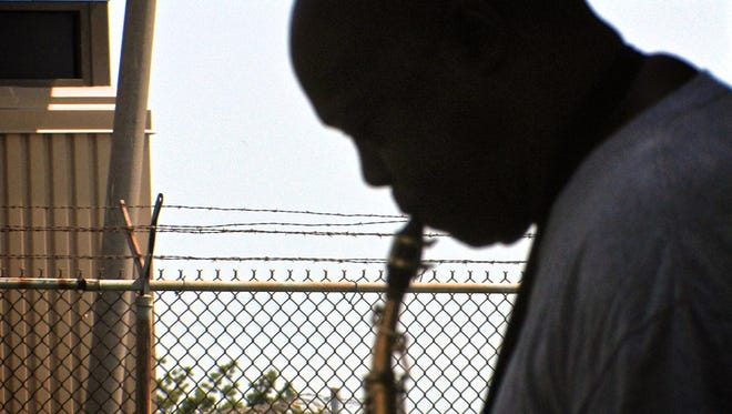 """Leotha Brown plays his saxophone behind bars in the documentary, """"Follow Me Down: Louisiana Prison Musicians."""""""