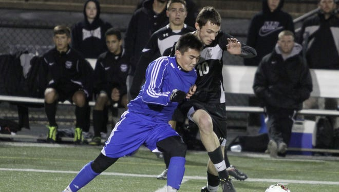 Zach Thomas of St. X leans on Logan Jatzek of Lakota East while going for the ball.  St. X and Lakota East meet in the Regional Semifinal at Sycamore Middle School on a chilly Wednesday night.