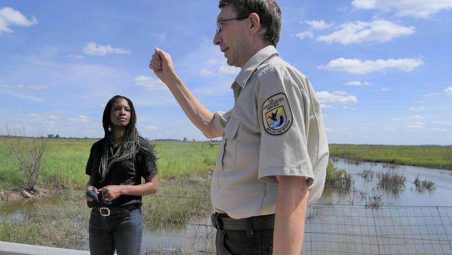 The director of the U.S. Fish and Wildlife Service, Aurelia Skipwith, left, listens as Mark Oldham, the manager of Quivira National Wildlife Refuge, tells a crowd of stakeholders about the refuge on July 25.