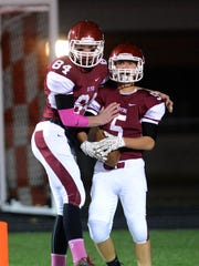 De Pere's Sam Janssen (5) is congratulated by teammate Connor Rutherford after scoring a touchdown on the opening kickoff against Green Bay Southwest in Friday's game at De Pere.