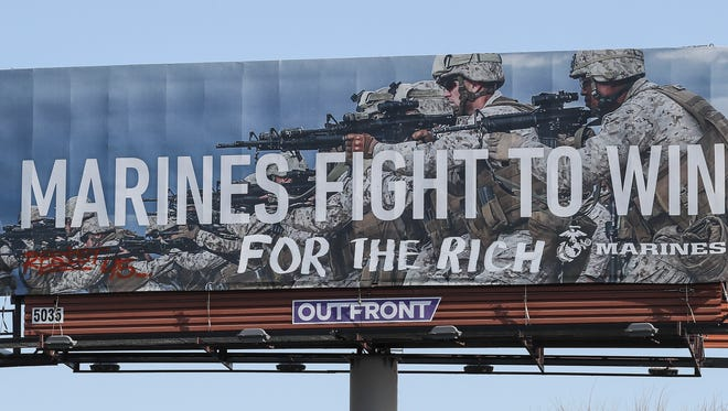 "A vandalized billboard that includes a ""Resist 45"" graffiti tag."