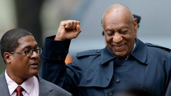 Bill Cosby pumps his fist in greeting as he arrives at court Wednesday shortly before jurors began deliberating the case.