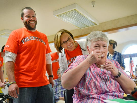 Good Shepherd Community resident Judith Yorek shares a laugh and a photo with United Way Day of Caring volunteers Chris Undersander and Michelle Bellrichard, both of Minnwest Bank, Thursday, Sept. 22, 2016, as she tries some chicken wild rice soup during the pub crawl.