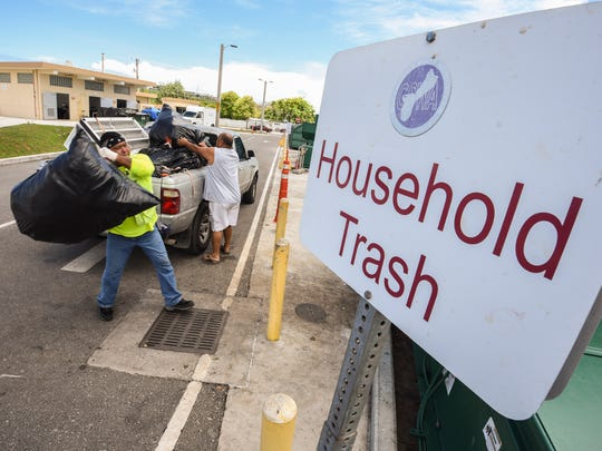 In this May 10, 2018, file photo, sanitation worker Gerald Castro helps Harmon resident Virgilio Sunga transfer bags of household trash into a compactor bin at the Guam Solid Waste Authority's Harmon Residential Transfer Station.