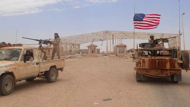 In this photo taken May 23, 2017, provided by the Syrian anti-government activist group, the Hammurabi's Justice News, which has been authenticated by AP reporting, shows a U.S.-backed anti-government Syrian fighter standing on a vehicle with heavy automatic machine gun, left, next of an American soldier who also stands on his armored vehicle.