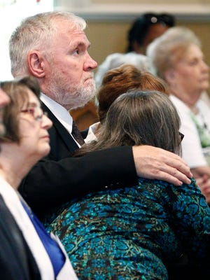 Relatives of Sister Margaret Held listen to the Rev. Greg Plata, who ministers at the Lexington church where Held and Sister Paula Merrill worshipped, deliver the homily during a memorial Mass for them Monday in Jackson.