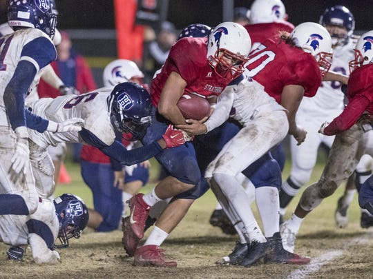 Strathmore's Joseph Garcia pushes Horizon Christian Academy defenders at least a dozen yards for a first down in a CIF Regional Football Championship Bowl Game in 2016.