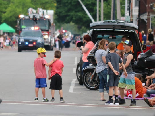 Kids eagerly await the Grande Parade along Second Street in Port Clinton during the Walleye Festival.