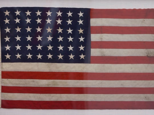 The state Capitol Museum plans to re-unveil an oil-stained American flag that sunk with the ship at Pearl Harbor seven decades ago. This photo was taken at Polly Rosenbaum State Archives and History Building in Phoenix on Nov. 6, 2014.