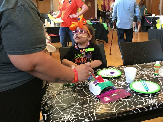 Esmeralda DeLosSantos, 2, and her mother, Stephanie DeLosSantos paint a Halloween mask at Driscoll Children's Hospital during a Halloween party Tuesday, Oct. 17, 2017.