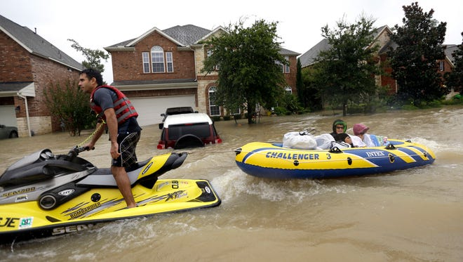 Flood victims are towed to safety as floodwaters from Tropical Storm Harvey rise Monday, Aug. 28, in Spring, Texas.