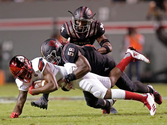 Louisville's Corey Reed runs the ball while North Carolina State's Airius Moore and Tim Kidd-Glass, right, move in for the tackle during the first half of an NCAA college football game in Raleigh, N.C.
