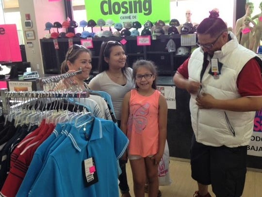 Raul Uriel, of Fort Worth, tries on a jacket at Holland's