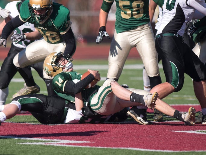 Windsor quarterback Seth Balch is brought down by Woodstock