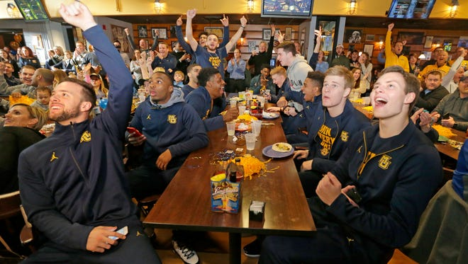 Marquette players including Marquette Golden Eagles guard Katin Reinhardt (left) and center Matt Heldt (right) celebrate with teammates upon learning they had earned the No. 10 seed in the NCAA Tournament's East Region and will face No. 7 South Carolina.