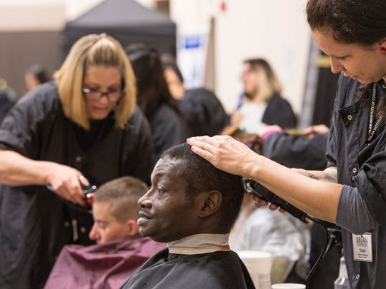 In this 2018 photo,  Milan Institute of Cosmetology student Nicole Shaw gives Maurice Williams a haircut.