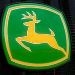 FILE - This June 8, 2014 file photo shows the John Deere farming logo at a farming equipment dealership in Petersburg, Ill. Even though sales of its green tractors, dozers and other equipment fell sharply, Deere & Co. reported better-than-expected fourth-quarter earnings as it cut costs. Also Wednesday, Nov. 25, 2015, the Moline, Illinois-based company posted an earnings outlook for the year that surpassed Wall Street expectations and its shares rose in premarket trading.  (AP Photo/Seth Perlman, File)