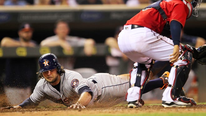 Houston Astros center fielder Jake Marisnick slides past Minnesota Twins catcher Kurt Suzuki to score on a sacrifice fly in the ninth inning Tuesday in Minneapolis. The Astros defeated the Twins 7-5.