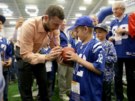 Quarterback Andrew Luck uses his throwing arm to sign a ball for cancer patient Kale Galloway in April. Luck not thrown since the end of last season,