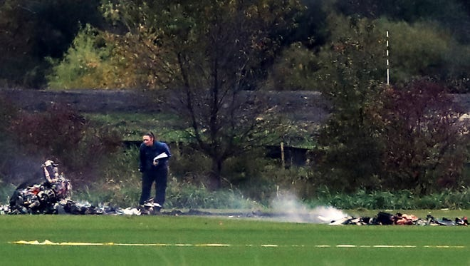 """An investigator looks over the scene where a helicopter crashed in a field   in Lino Lakes, Minn., on Thursday, Oct. 6, 2016.  Two people died when a helicopter erupted in """"a large fireball"""" as it crashed into a field in the Twin Cities suburb, a sheriff's official said Friday."""