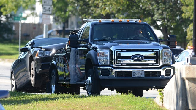 A tow truck removes an unmarked police car from the west end of the Don A. Tilleman Bridge on Sept. 23 after it collided with another marked cruiser.