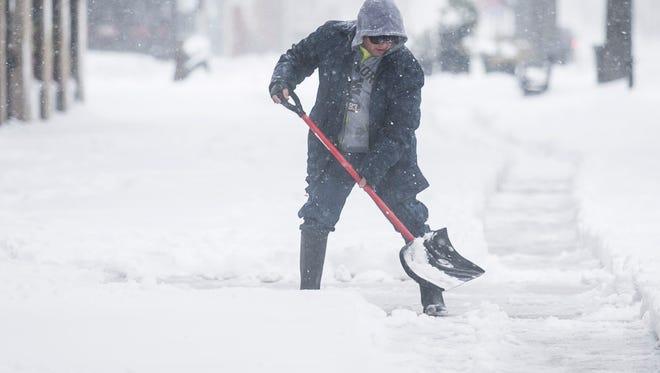 Julio Zeron, of York City, shovels part of the sidewalk, along W. Market St., Tuesday, March 14, 2017. Amanda J. Cain photo