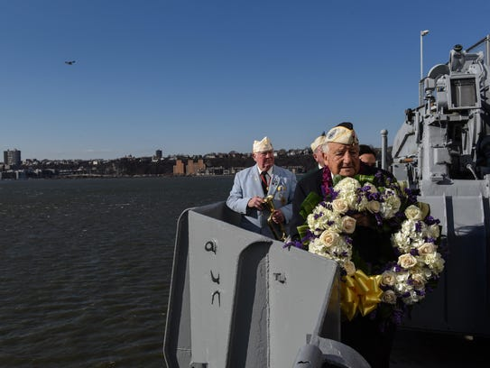 """Armando """"Chick"""" Galella holds a wreath at a wreath-laying"""