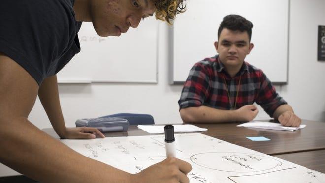 Joshua Hanson (left) and Ulises Gonzalez work on a physics problem, May 1, 2017, in their classroom at University High School, 9419 West Van Buren Street, Tolleson.