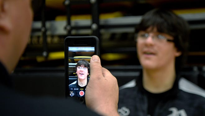 Robbinsville head wrestling coach Todd Odom films junior Jamie Kirl for a post on The Kirl Report, a Facebook page of video commentary after Black Knights' matches, following at match at Hayesville High School on Wednesday, Jan. 10, 2018. Kirl hopes to work in sports broadcasting after high school.