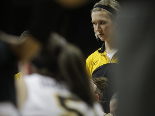 Iowa's Hailey Schneden listens to head coach Lisa Bluder during a timeout in the Hawkeyes' game against Michigan at Carver-Hawkeye Arena on Thursday, Jan. 22, 2015.