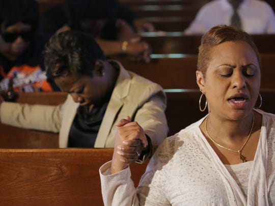 The Rev. Traci Blalock Phillips, 49, of Detroit holds hands with others during a prayer vigil held at the oldest African Methodist Episcopal church in Michigan, Bethel A.M.E. Church in Detroit, on Thursday, June 18, 2015, after the tragic shootings in Charleston, S.C.