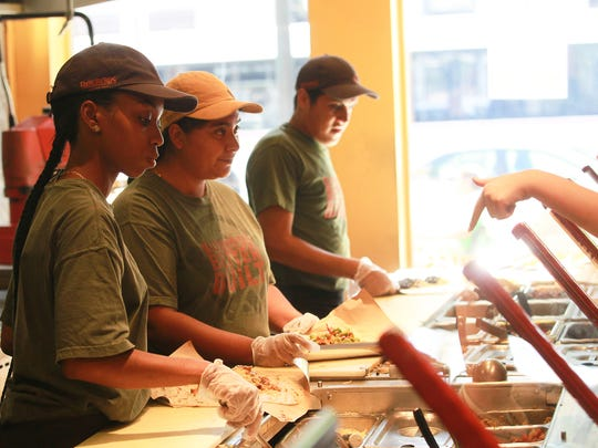 Pancheros employees prepare burritos for patrons in their Iowa City restaurant.
