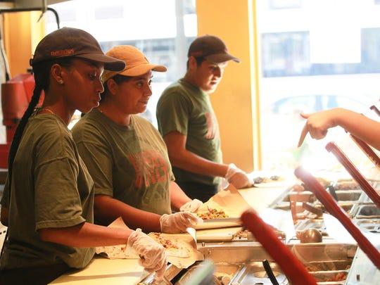 Pancheros employees prepare burritos for patrons in