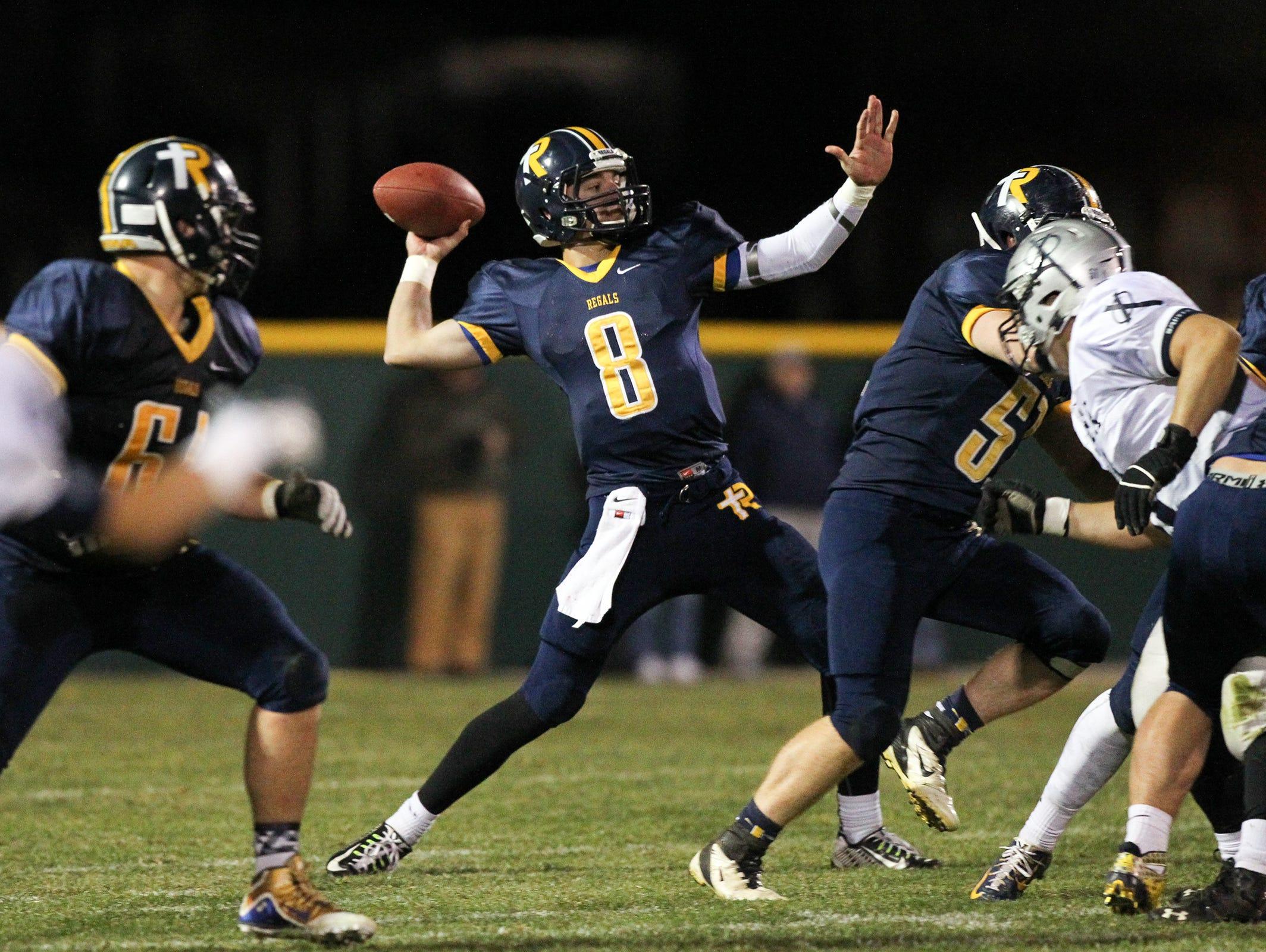 Regina quarterback Nate Stenger throws down field during the Regals' game against Cedar Rapids Xavier on Friday, Oct. 16, 2015.