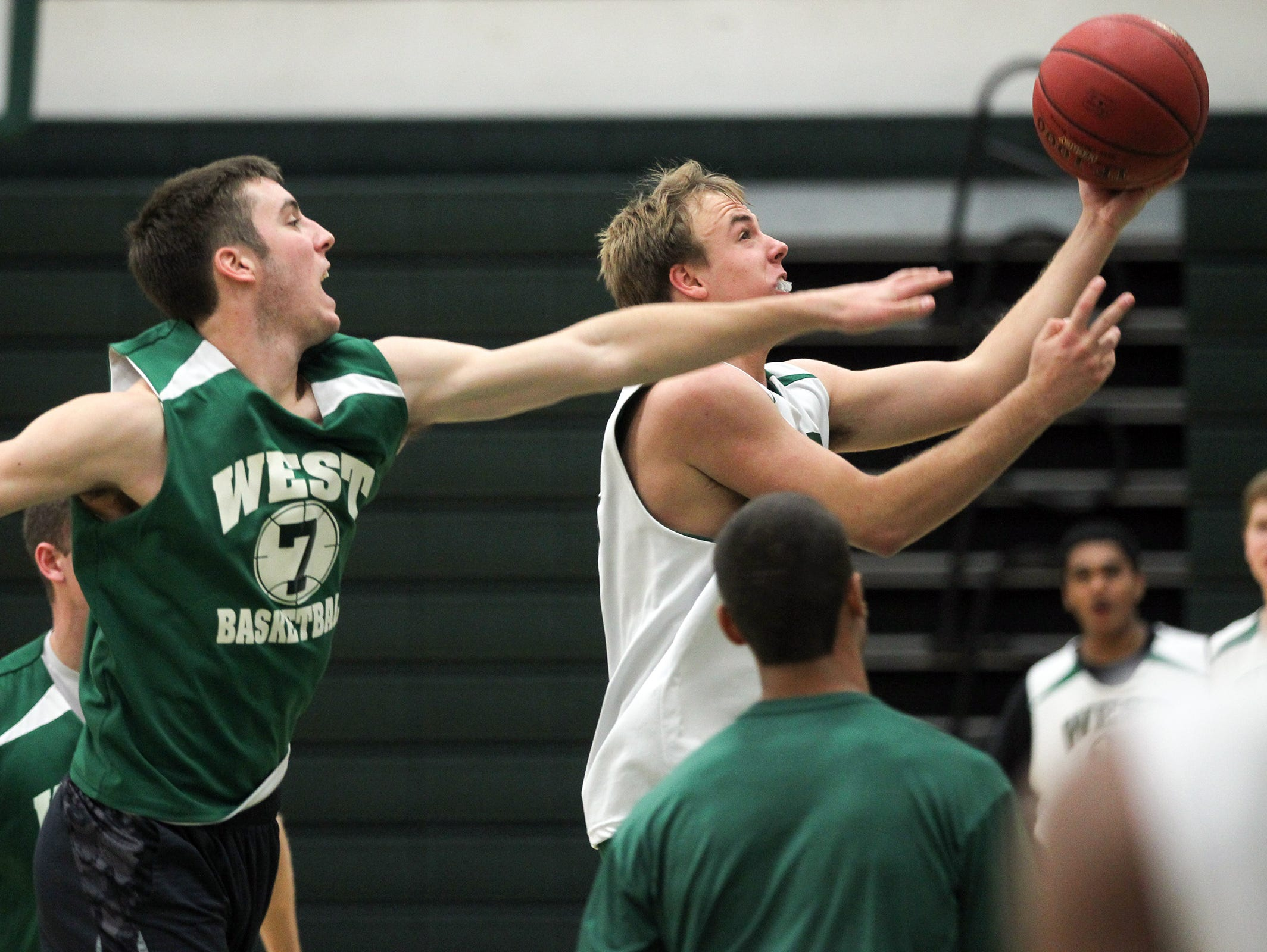 West High's Alex Henderson drives past Connor McCaffery during practice on Thursday, Nov. 19, 2015.