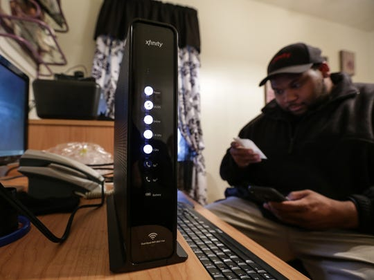 Comcast Cable Technical Operations Lead Technician Brandon Lofton works to install a new modem while setting up internet service and the X1 Operating system for a Detroit resident as they switch to Comcast on Friday November 27, 2015.