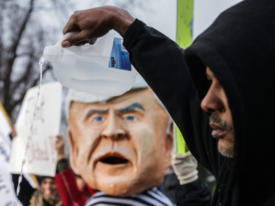 Preston Hamilton of Flint dumps out Flint drinking water he brought to a protest at Flint City Hall in downtown Flint on Friday, Jan. 8, 2016.