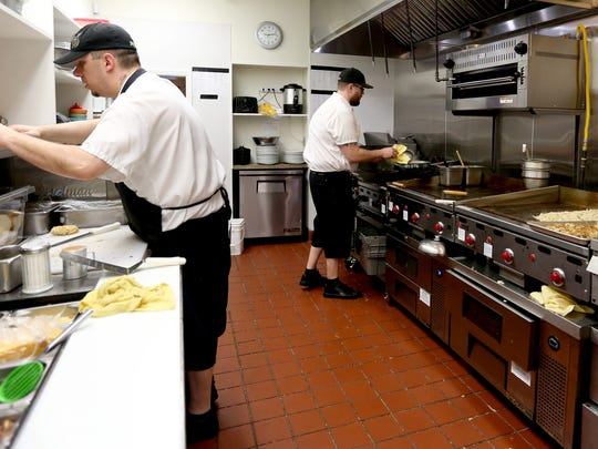 Justin Brunson, left, a cook, and Josh Haworth, the assistant kitchen leader, prepare meals at the Sassy Onion in Salem on Thursday, Jan. 21, 2016. The restaurant has reopened after a fire destroyed much of it in November.