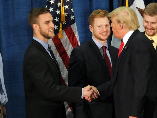 Republican presidential candidate Donald Trump greets members of Iowa's football team at the University of Iowa Field House in Iowa City at 8:31 p.m. Tuesday, Jan. 26, 2016.