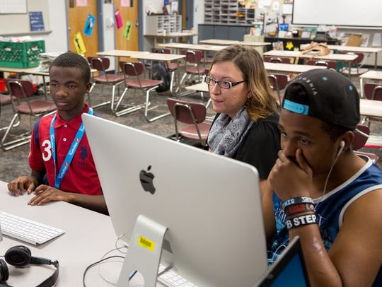 Teacher Heather Jancoski, center, helps R'bryon Anderson,