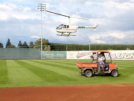 A helicopter lands on center field, part of a reenactment of the inaugural opening ceremonies, before the 20th anniversary season opener for Volcanoes baseball at Volcanoes Stadium in Keizer on Friday, June 17, 2016.