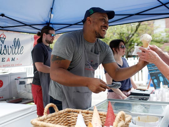 Darryl Goodner, center, serves his handmade ice cream to customers at the Douglas Loop Farmer's Market with the help of co-owners Zach Hardin, left, and Lynette Ruby, right.  Aug. 6, 2016