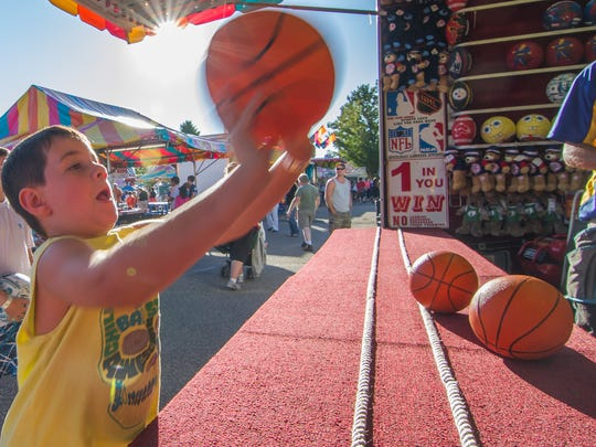 Parker Lemery, 7, of Shelburne tries his luck at a basketball game at the Champlain Valley Fair in 2013.