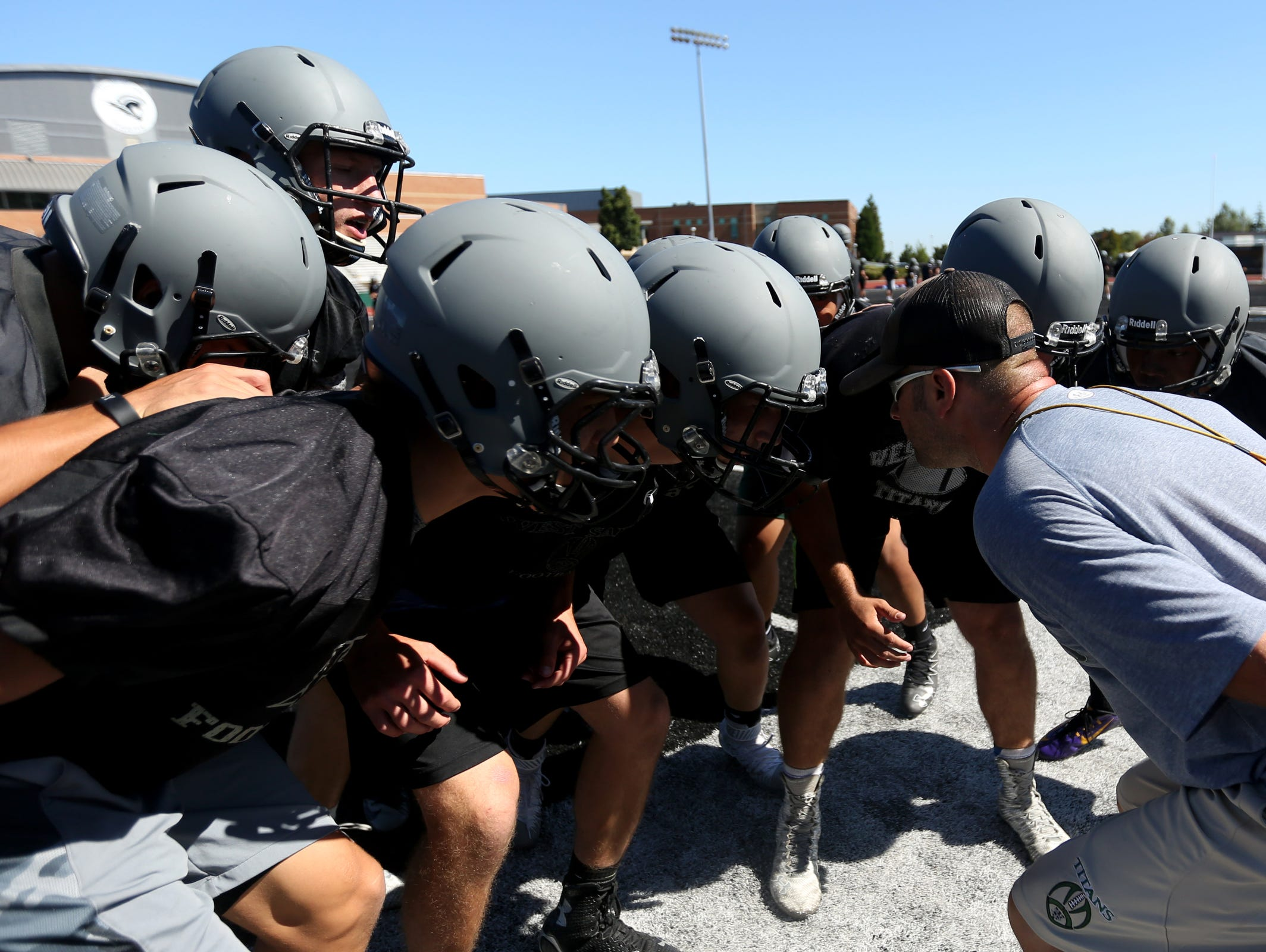 Chris Vandiver, the linebacker coach, leads a drill during football practice at West Salem High School on Monday, Aug. 15, 2016.