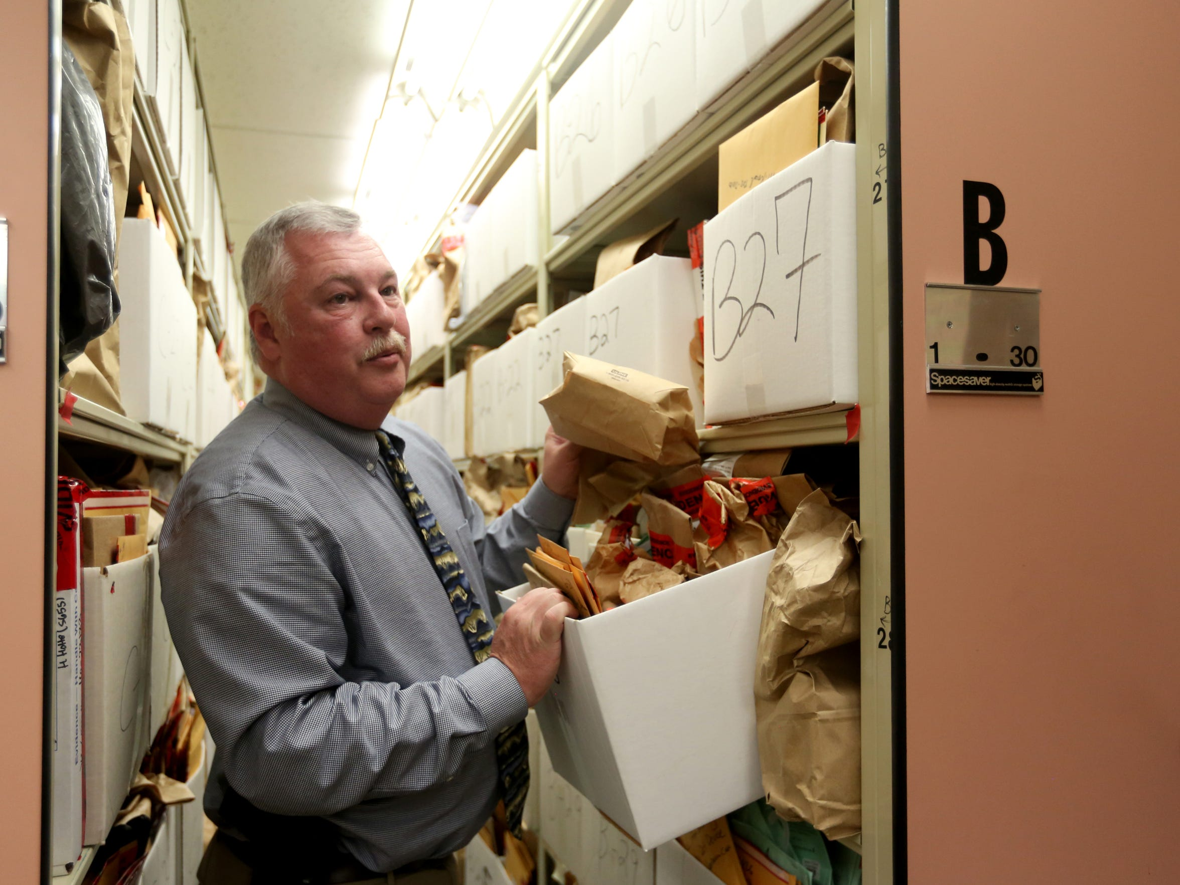 Deputy Chief Steve Bellshaw look through evidence boxes at the Salem Police Department facility at City Hall on Friday, Oct. 14, 2016.