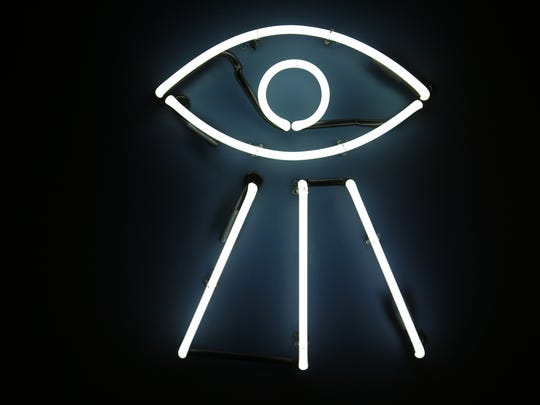 A neon Eye of Providence greets guests to the Bad Luck