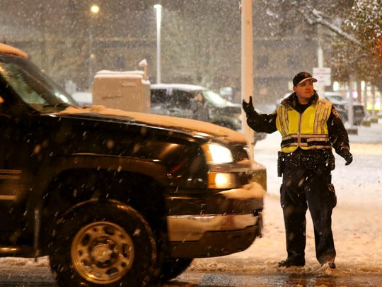Police meter traffic onto the Marion Street Bridge in an attempt to prevent pileups as snow falls over Salem on Wednesday, Dec. 14, 2016.