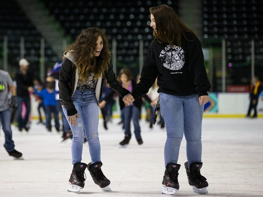 Kristen Bernal (left) and Felicity Rivera laugh as they skate on the ice during American Bank Center's Winter Wonderland Skating & Holiday Event on Thursday, Dec. 22, 2016.