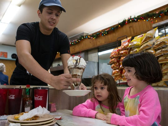 Waiter Damien Rivera delivers an ice cream sundae to five-year-old Rose and three-year-old Genevieve de la Garza during lunch service at Hamlin Pharmacy and Fountain on Thursday, Dec. 29, 2016.